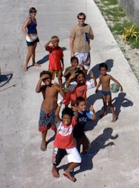 Kids watching kite aerial photos being taken in Manihi